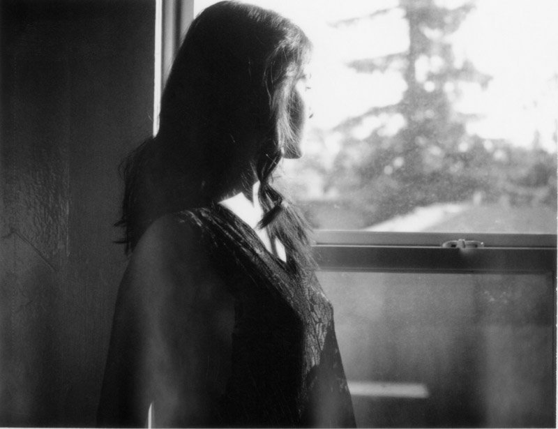 Fine art image of woman looking out a window on polaroid film.