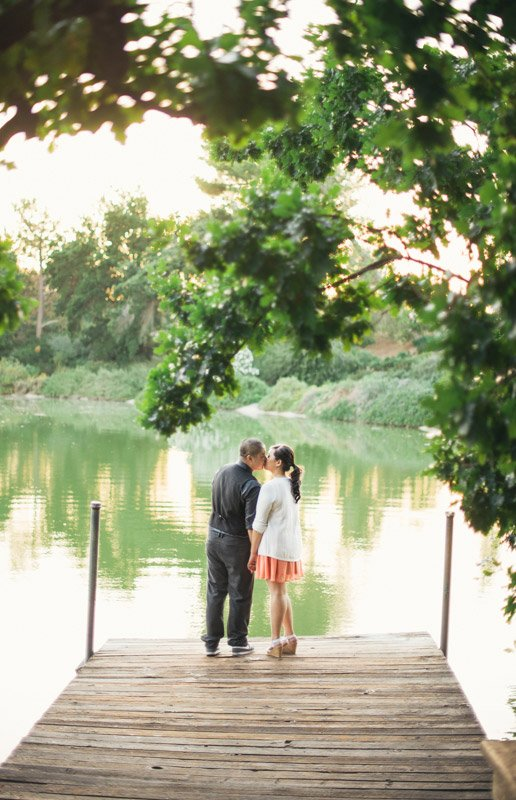Engagement image of couple kissing on dock at sunset.