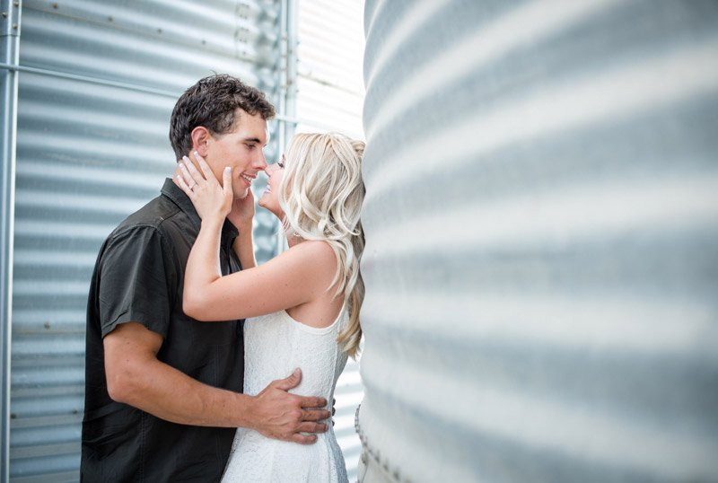 Couple kissing against silo