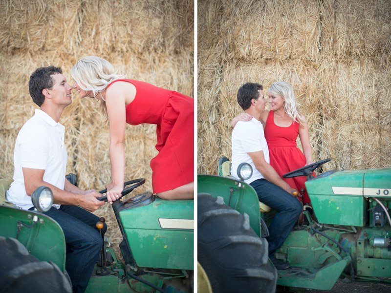 Engaged couple posing with John Deere tractor