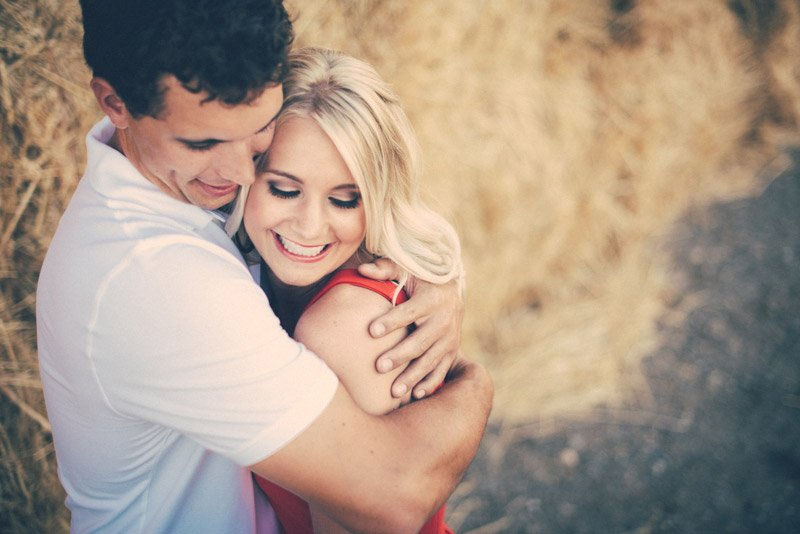 Engaged couple hugging in front of hay bales