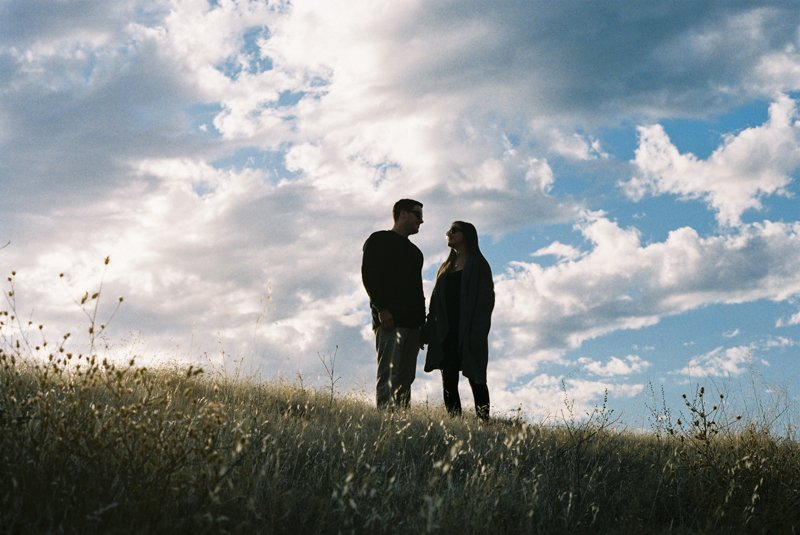 silhouette of couple against epic sky captured on 35mm film