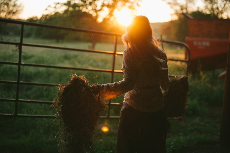 lifestyle-portrait-of-woman-moving-hay-at-sunset