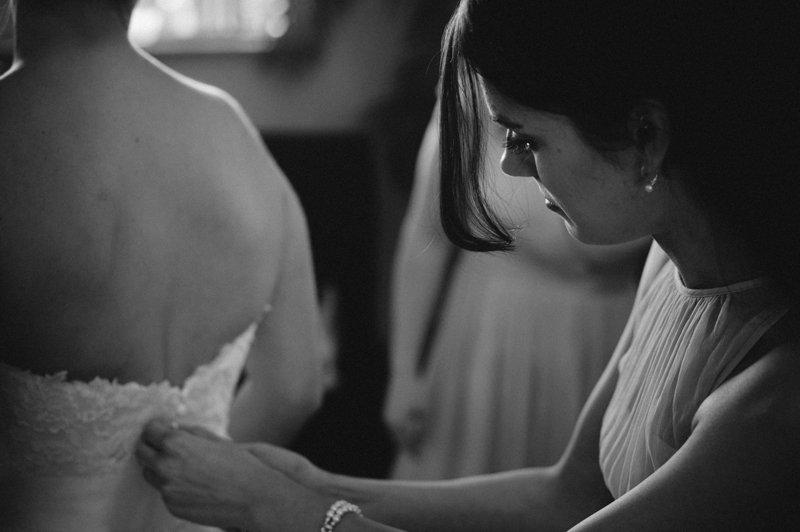 bridesmaid-helping-bride-get-ready-at-white-ranch
