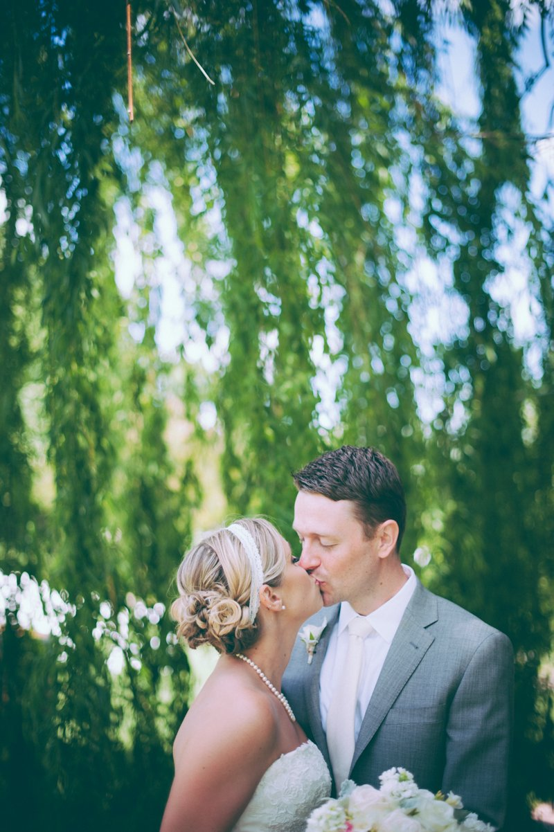 bride-and-groom-kissing-under-willow-tree