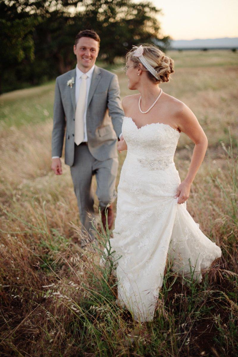 bride-walking-through-tall-grass-at-sunset